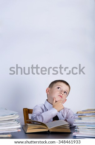 Little child thinking leaning on pile of books, isolated grey background.Thoughtfully child with a stack of books leaning on them.Education concept - stock photo