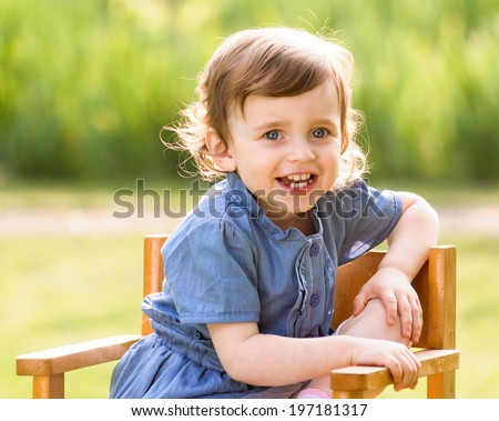 little child, toddler girl in outdoors in the garden sitting on a chair on a sunny summer day - stock photo