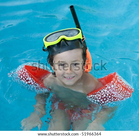 Little child with diving goggles and snorkel swimming in the water - stock photo