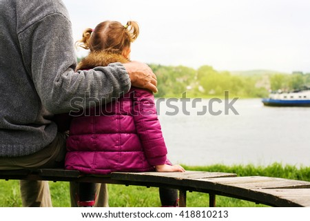Little child with her grandpa spending time near the river. Rear view.  - stock photo