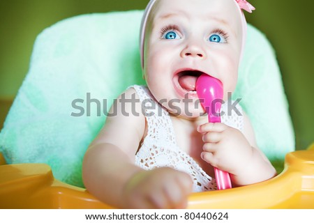 little child with pink spoon in mouth - stock photo