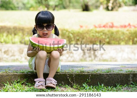 Little child with sunglasses and big slice of watermelon sitting in the park - stock photo