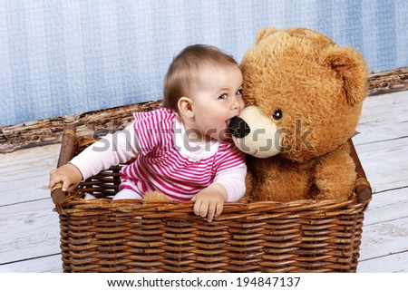 Little child with teddy bear sitting in the basket - stock photo