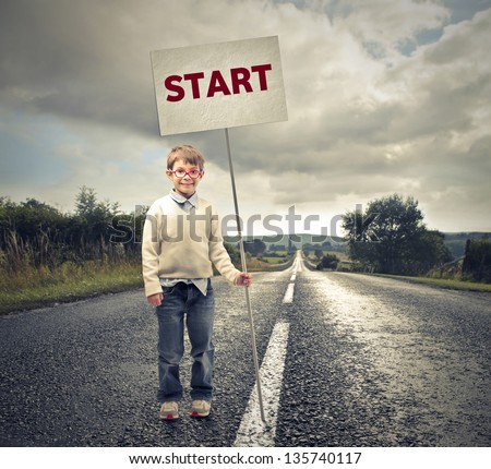 little child with with a sign on the road - stock photo