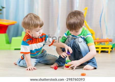 little children boys playing with toys at home - stock photo