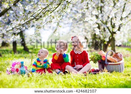 Little children eating lunch outdoors. Kids with picnic basket in spring garden with blooming apple and cherry tree. Preschooler girl, toddler boy and baby eat and drink in summer park on blanket. - stock photo