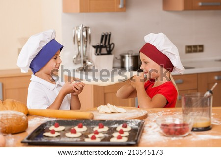 little children making bakery and playing. brother and sister having fun at kitchen table  - stock photo