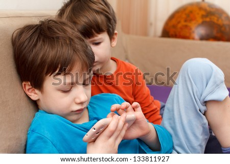 Little children playing with smartphone - stock photo