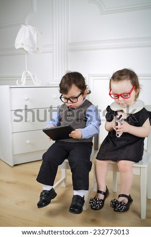 Little children sitting on white chairs: boy in black glasses with tablet computer and girl in red glasses with mobile phone - stock photo