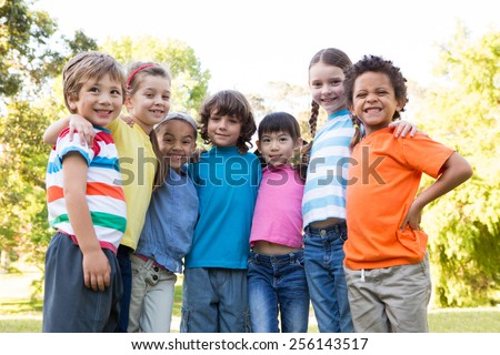 Little children smiling at camera on a sunny day - stock photo