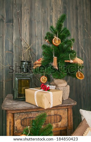 Little Christmas Tree on the table with a gift - stock photo