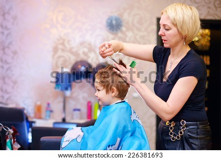 little client, boy having haircut at hair salon - stock photo