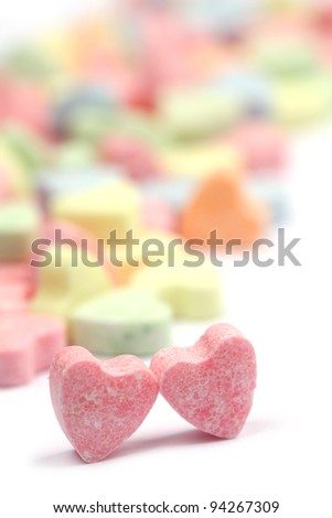 Little colorful candy hearts on white background. Shallow dof - stock photo
