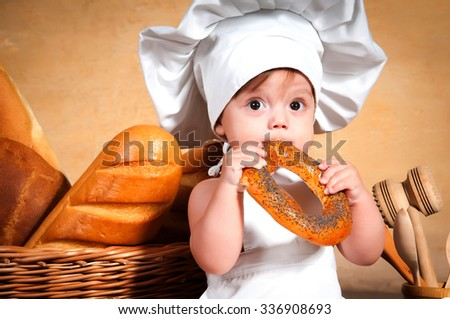 Little cook in a chef's hat eating a bagel. Close-up portrait. - stock photo