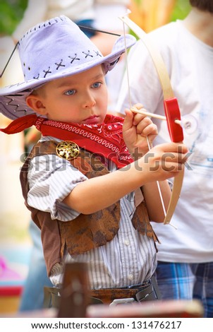 Little cowboy shoots a bow with serious calm gaze - stock photo