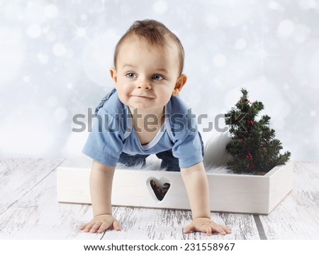 Little crawling baby boy with christmas tree - stock photo