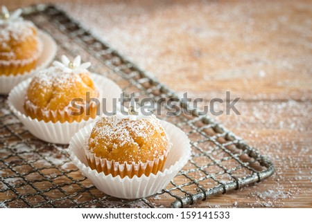 Little cupcakes decorated with powdered sugar and little gumpaste flowers. Selective focus  - stock photo