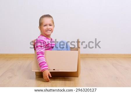 Little curious girl in cardboard box - stock photo