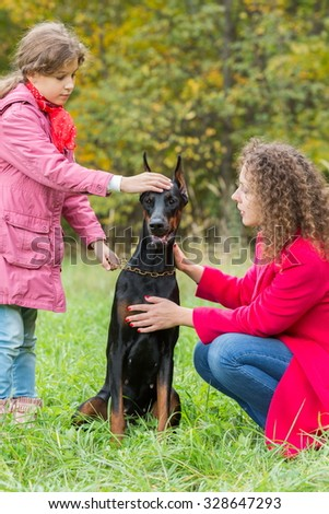 Little curly girl and her mother are walking the dobermann in park. - stock photo