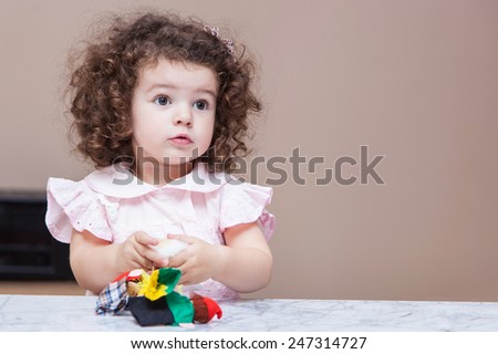 Little curly girl playing with a doll - stock photo