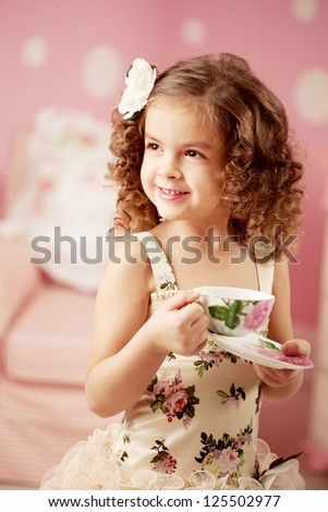 Little cute and sweet girl with tea - stock photo