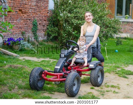 Little cute baby boy driving pedal car with young beautiful mother in the garden - stock photo
