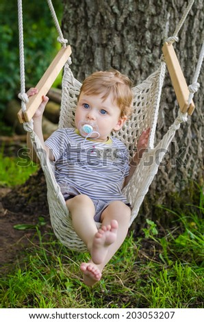 Little cute baby boy riding on a hammock swing in the park - stock photo