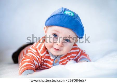 Little cute baby lying on the white blanket looking straight to the camera - stock photo