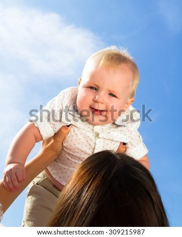 Little cute baby outdoor.A cute child outside at sky background (copy space).Adorable toddler boy in the park.Summer portrait of happy baby girl infant outdoors at park.Baby wearing white shirt. - stock photo