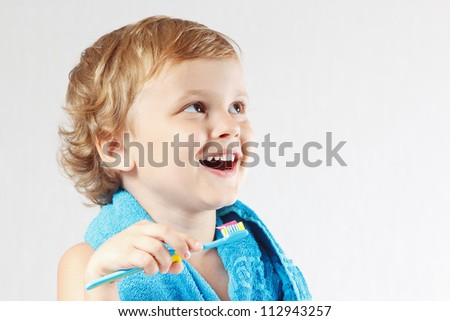 Little cute blond boy brushing his teeth on a white background - stock photo