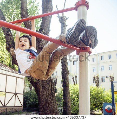 little cute blond boy hanging on playground outside, alone training with fun, lifestyle children concept - stock photo