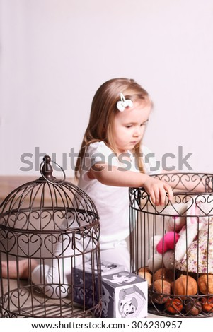 Little cute blond girl sitting in room and playing with toys and cages. Focus on cage - stock photo