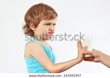 Little cute blonde boy refuses drink a fresh milk - stock photo