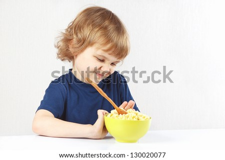 Little cute blonde boy refuses to eat a cereal - stock photo