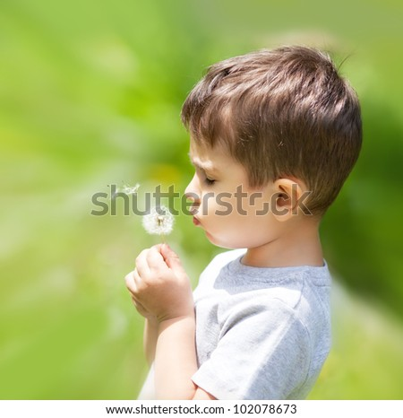 Little cute boy blowing dandelion on blurred nature background - stock photo