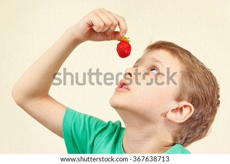 Little cute boy eating a fresh ripe strawberry - stock photo