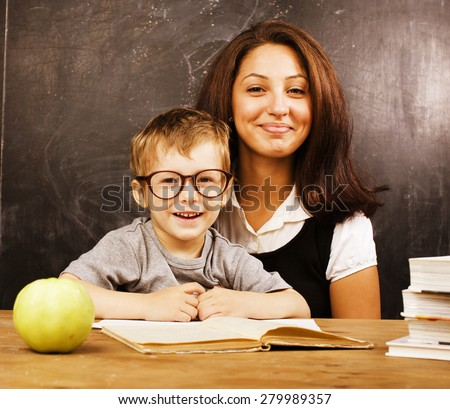 little cute boy in glasses with young teacher, classroom studying  - stock photo