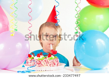 Little cute boy in holiday hat with a birthday cake with whistle and festive balloons - stock photo