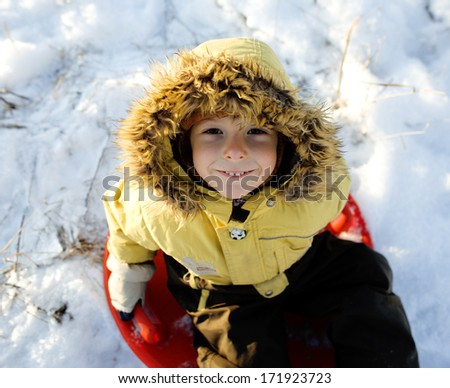 little cute boy in hood with fur on snow outside - stock photo