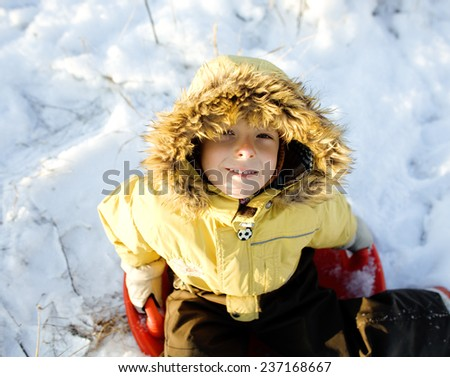 little cute boy in hood with fur on snow outside smiling - stock photo
