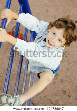 little cute boy playing on playground, hanging on gymnastic ring - stock photo
