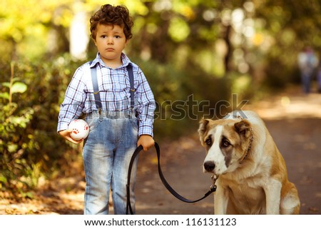 little cute boy playing with his dog in the autumn park - stock photo