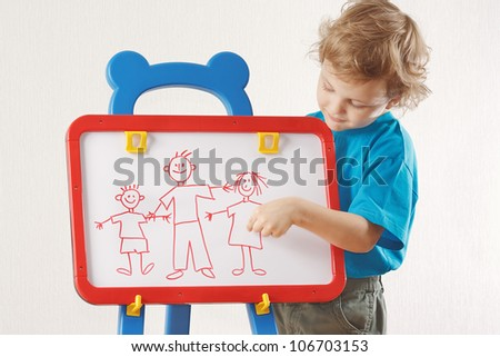 Little cute boy shows his family painted on a whiteboard - stock photo