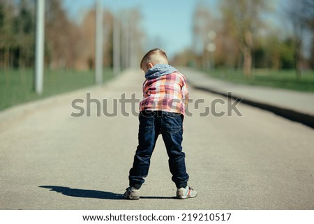 little cute boy stay back and ape on the street - stock photo