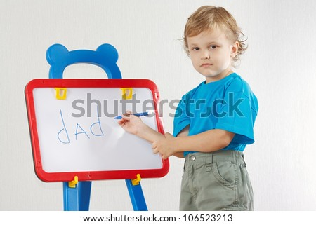 Little cute  boy wrote the word dad on whiteboard - stock photo
