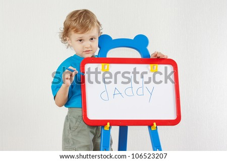 Little cute boy wrote the word daddy on whiteboard - stock photo