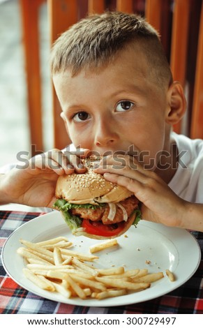 little cute boy 6 years old with hamburger and french fries making crazy faces in restaurant close up - stock photo