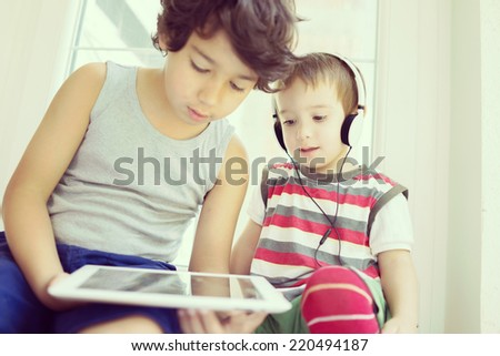 Little cute boys having fun time using tablet at living room - stock photo