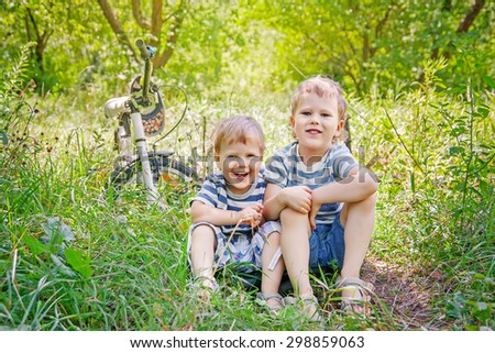Little cute brothers sitting in the grass - stock photo