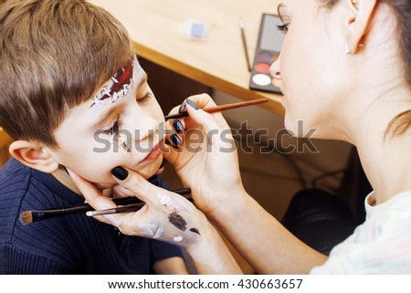 little cute child making facepaint on birthday party, zombie Apocalypse facepainting, halloween preparing concept - stock photo